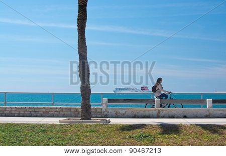 Woman riding a bike along the Paseo Maritimo