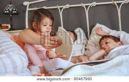Baby girl reading book with family in the bed