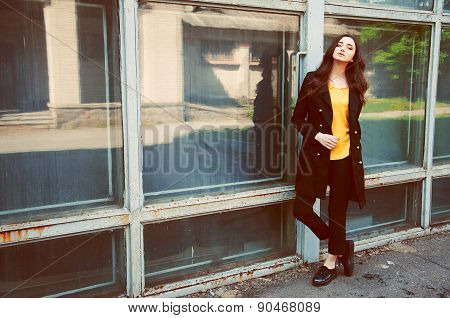 Young Woman Portrait In Black Trenchcoat And Yellow Blouse