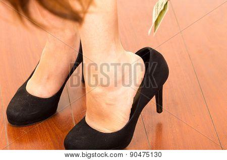 Superstitious woman's hand putting a dollar bill inside shoe