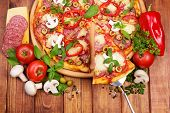 Supreme Pizza with tasty slice on wooden table background poster