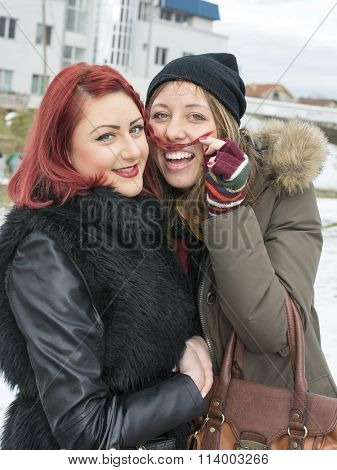 Two Girls Posing For A Funny Portrait In Winter