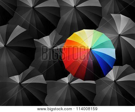 multicolored umbrella against other black umbrella