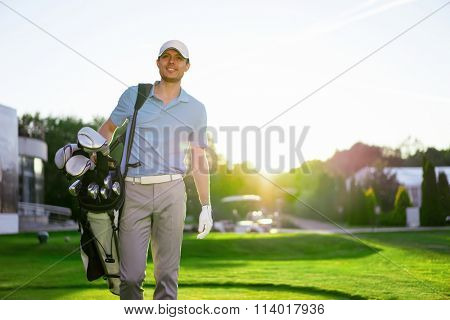 Golfer with club on a lawn