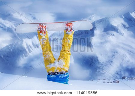 Legs of a snowboarder in yellow trousers stuck in deep snow upside down