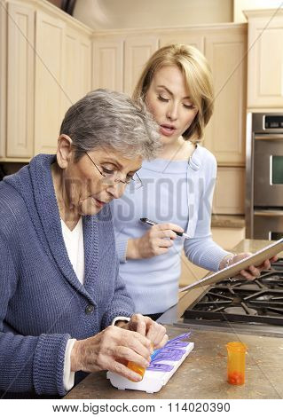 Elderly Woman Getting Help Organizing her prescription medicine into a pill box by