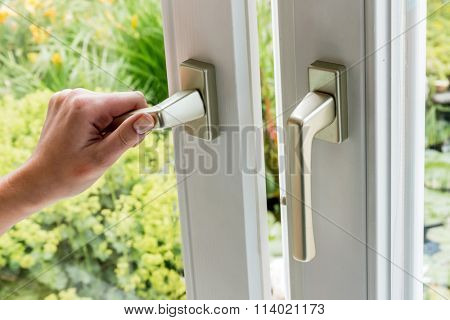 woman opens window for ventilation