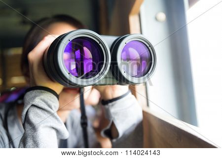 Woman looking though binoculars for birdwatching