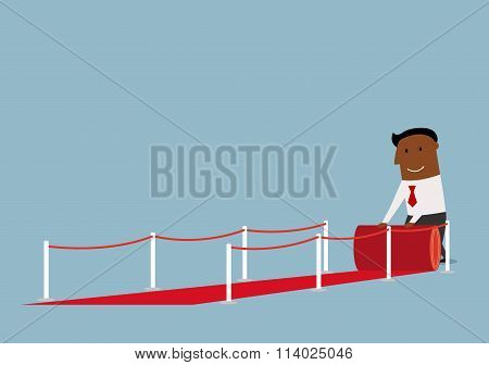 Happy businessman unwinding a roll of red carpet