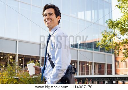 Happy young businessman walking and holding laptop bag and coffee paper cup. Satisfied businessman looking away with modern buildings in background. Happy smiling man going to work.