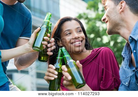 Closeup shot of young friends toasting with bottles of beer. Multiethnic people drinking beer. Happy mem and women smiling and drinking a beer for the aperitif.