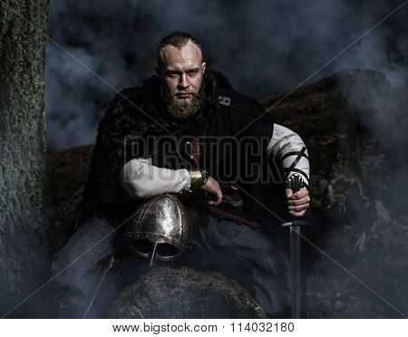 Viking With Sword And  Helmet On A Background Of Smoky Forest