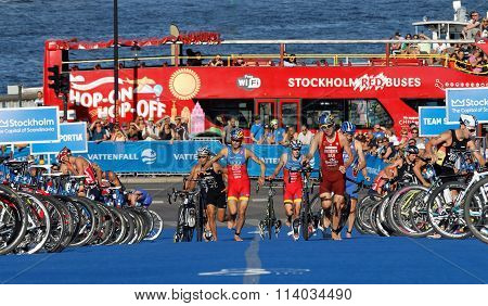 STOCKHOLM SWEDEN - AUG 23 2015: Triathletes Mola and Riederer running uphill with bicycles in the transition zone bus and sea in the background in the Men's ITU World Triathlon series event August 23 2015 in Stockholm Sweden