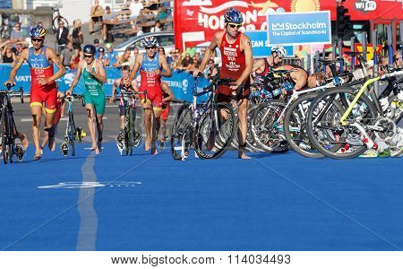 STOCKHOLM SWEDEN - AUG 23 2015: Triathletes Mario Mola and Alarza running with bicycles others parking cycles in the transition zone in the Men's ITU World Triathlon series event August 23 2015 in Stockholm Sweden