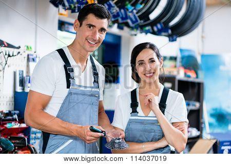 Woman and man as bike mechanics in workshop