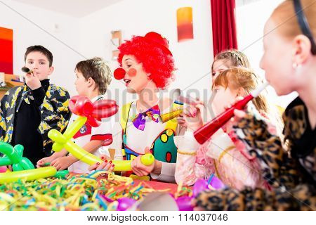 Children celebrating birthday party with noisemakers while a clown is visiting entertaining the kids