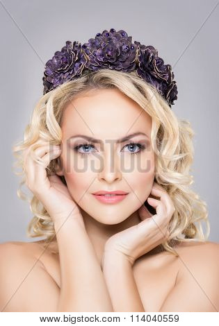 Close-up of young, sensual woman wearing purple flower alike coronet over grey background.