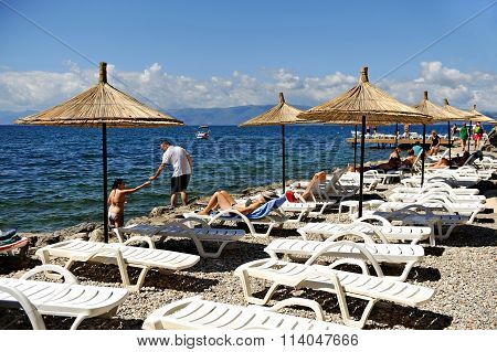 Tourist Sunbathing On Ohrid Lake Shore In Summer