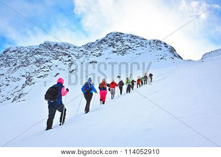 Group Of Tourists To Climb On A Snowy Mountain Pass