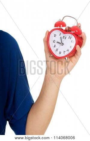 Young woman holding alarmclock.