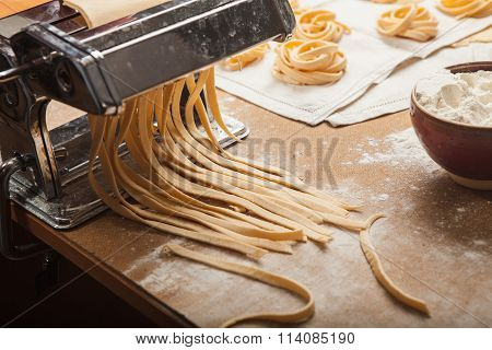 The fresh pasta and  machine on kitchen table