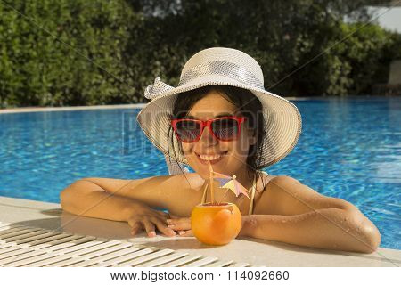 Pretty female drinking grapefruit juice at the edge of a swimming pool