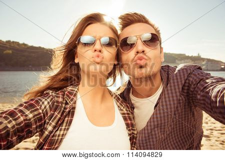Couple In Love Making Selfie Photo At The Seaside With Kiss, Close-up Photo