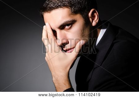 Young businessman in dark studio