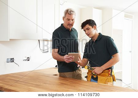 Carpenter And Apprentice With Digital Tablet Fitting Luxury Kitchen