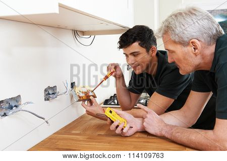 Electrician With Apprentice Working In New Home poster