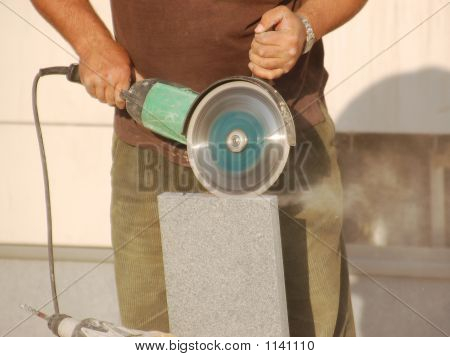 construction worker cutting concrete block using circular saw poster
