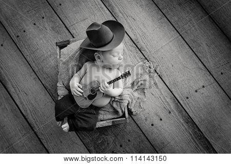 Newborn Baby Cowboy Playing A Tiny Guitar