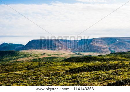 Green Hills With Forest Against Plateau Under Cloudy Sky