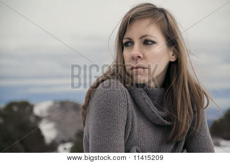 A sad, lonely brunette gazing over shoulder at beautiful snow landscape