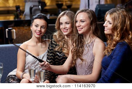 women with smartphone taking selfie at night club