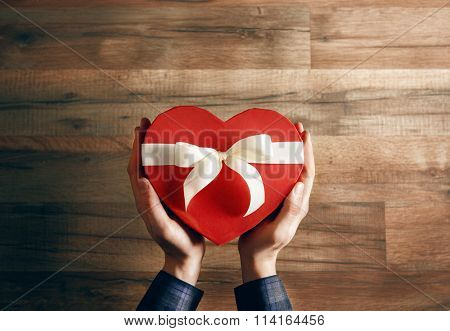 male hands holding a gift in the shape of a heart. the concept of love and Valentine's day