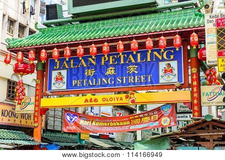 KUALA LUMPUR, MALAYSIA - SEPTEMBER 18, 2015: Crowds pass below the main gate of Chinatown at Petaling Street.