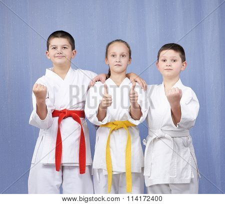 Boy and girl standing in rack of karate and showing the finger super