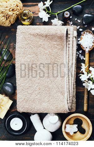 Spa background (white orchid, herbal compress stamps, sea salt, towel, candle and massage stones)