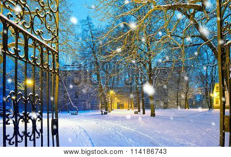 Winter Park With Gateway In The Snowfall By Night, Town Of Postoloprty, Czech Republic