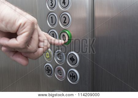 Forefinger pressing the zero floor button in the elevator
