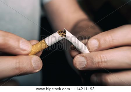 Quitting smoking - male hand crushing cigarette poster