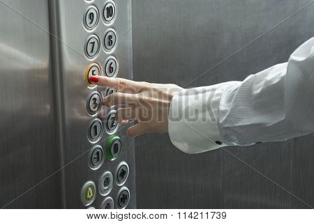 Female hand pressing the button in the elevator