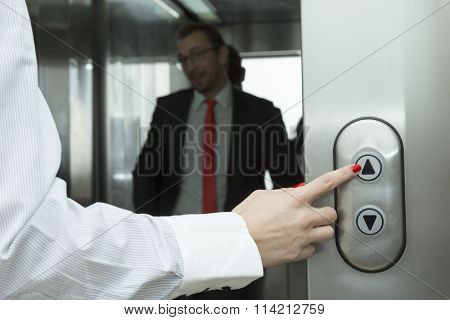 Female hand pressing elevator up button. Businessman inside of the elevator.