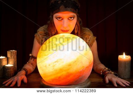 Young Pretty Fortune Teller With A Shining Crystal Ball And Candles