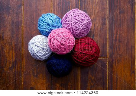 Pile Of Skeins In Red And Pink Tones Over Wooden Background