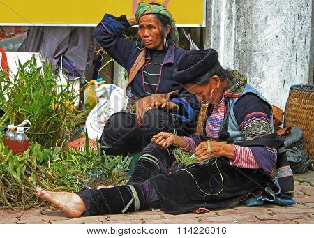women in a traditional clothes are sewing, Sa Pa, Vietnam
