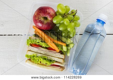 Lunchbox with sandwich, vegetables and fruit, bottle of water on a white background