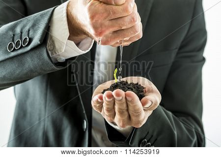 Businessman Watering And Nurturing A Green Sprout Growing From A Fertile Soil He Is Holding In His C