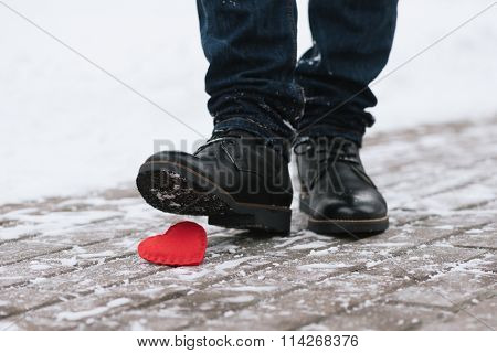 Tramples love. Symbol of separation. A man stepped on a shoe decorative heart